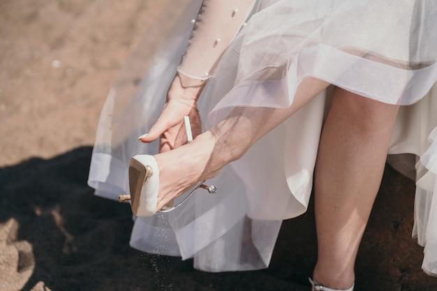 花嫁は靴を履く女の子はかかとのある靴を履くのにうんざりしていました女性は靴を脱いでいます...