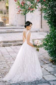 Невеста с букетом невесты стоит под цветущим олеандром возле старой церкви