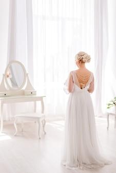 Невеста спиной к окну в яркой студии на фоне туалетного столика. на ней длинное белое платье с открытой спиной и бусинами, жемчугом. утро невесты