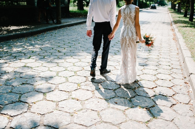 ウェディングブーケと新郎の花嫁が歩道に戻る