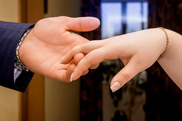 花婿は彼女の手で花嫁の手を握る。