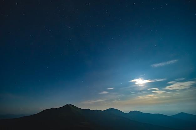산 위의 별이 빛나는 하늘에 밝은 달