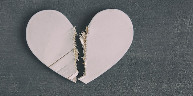 木製のテーブルの上の壊れた白い木製の心。離婚の概念、壊れた関係と愛の終わり