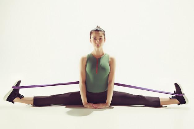 Брюнетка спортивная женщина упражняется с резиновой лентой