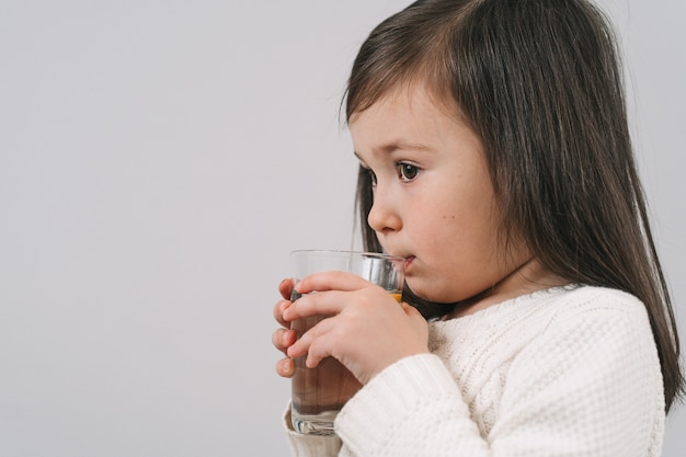 Брюнетка пьет воду из прозрачного стакана. девушка держит стакан с водой.