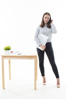 Брюнетка стоит рядом со столом и работает за компьютером на белом фоне