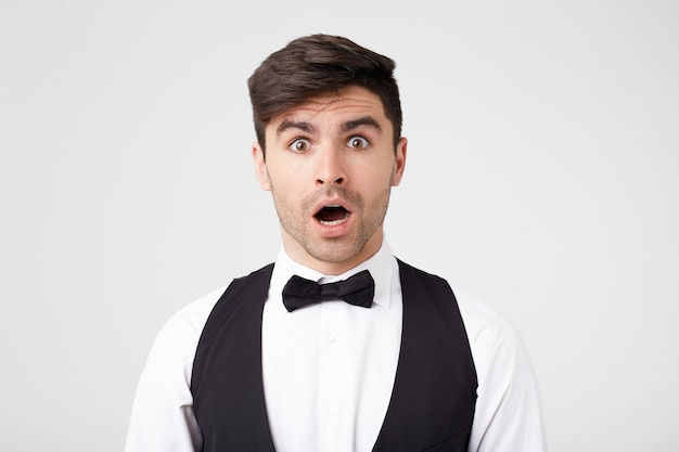 白いシャツ、ベスト、黒い蝶ネクタイをきちんと身に着けているブルネットの男は、ショックを受けているように見えます