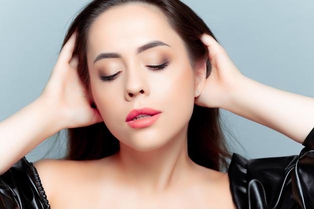 ブルネットのモデルの女の子は頭を後ろに傾けて目を閉じ、髪をまっすぐに戻しました