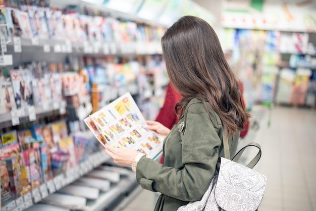 Брюнетка стоит в торговом центре возле полок журналов и смотрит на каталог продукции