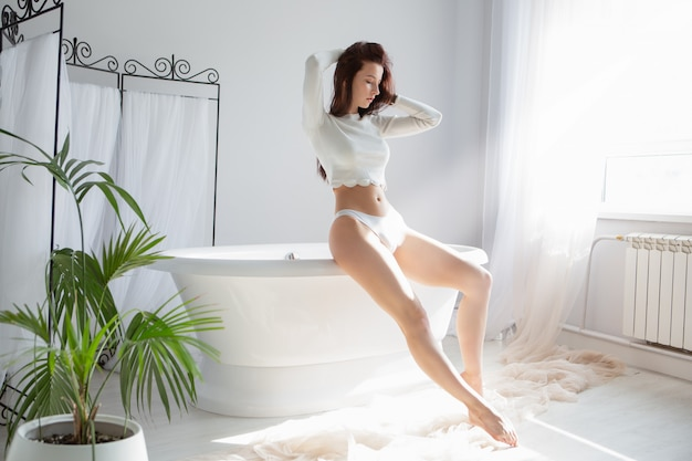 갈색 머리는 섹시한 속옷에 목욕에 앉아있는 동안 머리카락을 곧게 만듭니다.