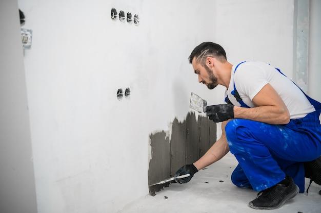 Строитель прикрепляет плитку к стене цементом. на нем синяя рабочая одежда и черные перчатки.
