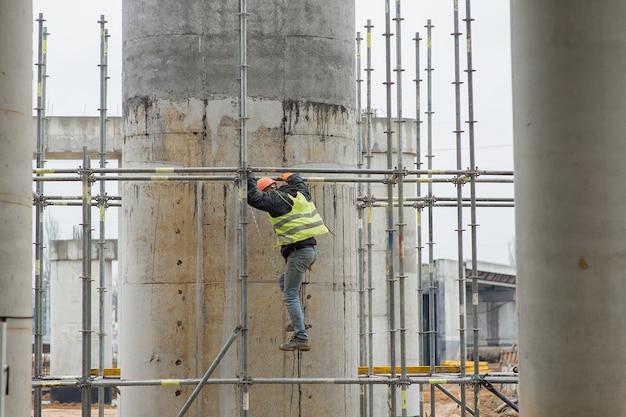 건축업자는 건설 현장에서 비계를 내려갑니다.