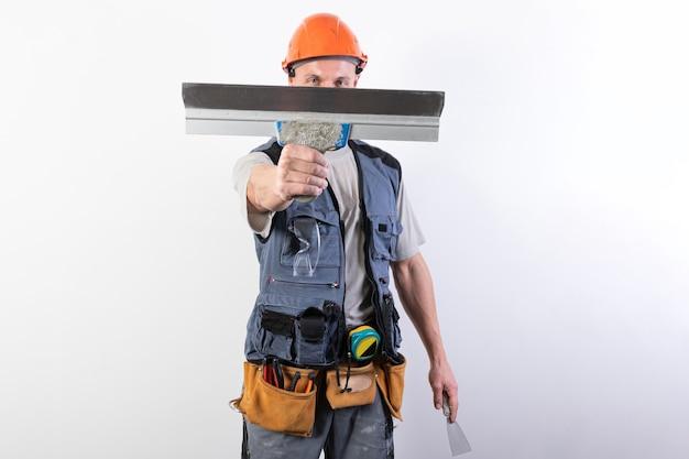 Строитель прячет лицо за шпателем в рабочей одежде и каске на светло-сером фоне