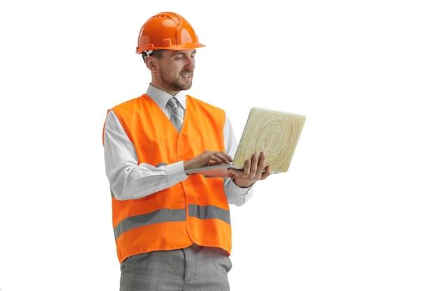 Строитель в строительном жилете и оранжевом шлеме с ноутбуком.