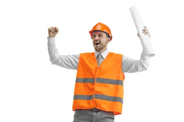 白いスタジオの背景に立っている建設ベストとオレンジ色のヘルメットのビルダー。安全スペシャリスト、エンジニア、業界、建築、マネージャー、職業、ビジネスマン、仕事の概念