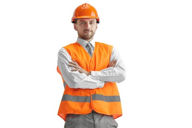 Строитель в строительном жилете и оранжевом шлеме, стоящем на белом фоне студии. специалист по безопасности, инженер, промышленность, архитектура, менеджер, род занятий, бизнесмен, концепция работы