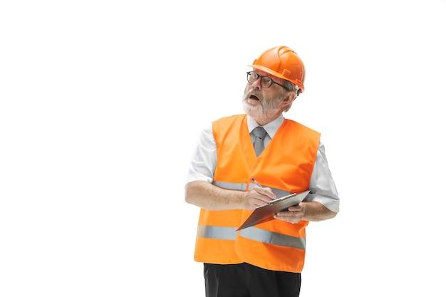 白いスタジオの背景に立っている建設ベストとオレンジ色のヘルメットのビルダー。安全スペシャリスト、エンジニア、業界、建築、マネージャー、職業、ビジネスマン、仕事のコンセプト