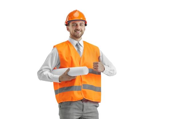 白いスタジオに立っている建設ベストとオレンジ色のヘルメットのビルダー