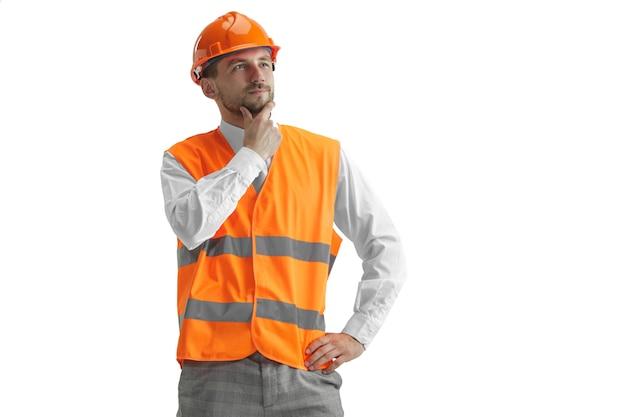 Строитель в строительном жилете и оранжевом шлеме, стоящем на белой стене. специалист по безопасности, инженер, промышленность, архитектура, менеджер, род занятий, бизнесмен, концепция работы