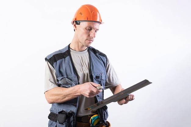 Строитель чистит шпателем. в рабочей одежде и каске. на светло-сером фоне. для любых целей.