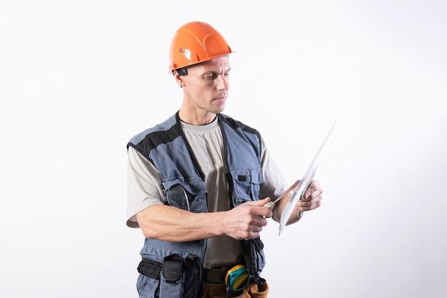 Строитель чистит шпателем в спецодежде и каске на светло-сером фоне.
