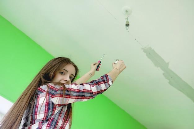 건축업자는 아파트를 수리합니다. 마무리 작업은 석고 및 벽 페인팅입니다. 마스터는 페인트 드릴과 전기로 작업합니다.