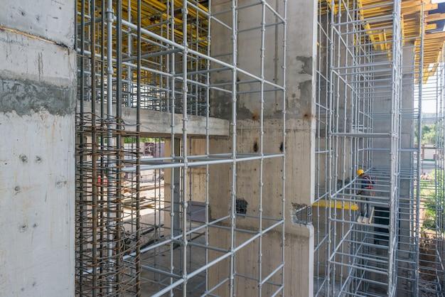 건축업자는 높은 비계에 서서 작업을 수행합니다.