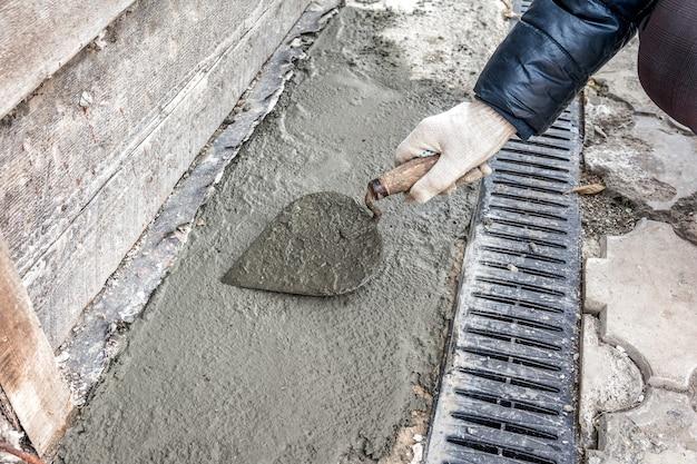건축업자는 집의 오래된 기초를 수리합니다 흙손으로 시멘트 모르타르를 평평하게 합니다
