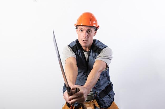 ビルダーは刀との戦いを示しています。ヘルメットと作業服を着た修理工。あらゆる目的のために。