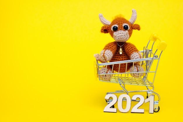 Бык - символ нового года 2021. вязаная игрушка бык в игрушечной тележке супермаркета.