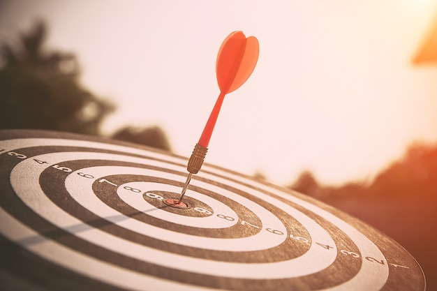 На яблочко, или на яблочко, или на доску для дартса стрелка дротика попадает в центр стреляющей мишени для достижения целей в бизнесе и достижения успеха.