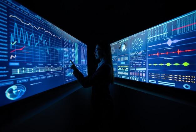 어두운 사무실에서 파란색 모니터 사이에 서 있는 비즈니스 여성