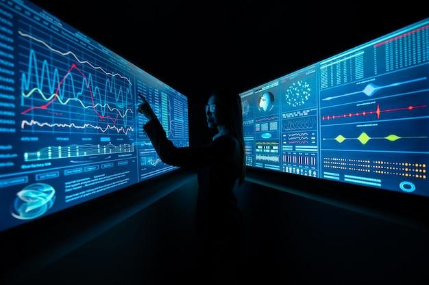 어두운 실험실에서 블루 스크린 사이에 서 있는 비즈니스 여성