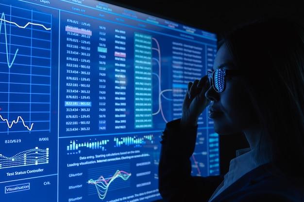 어두운 실험실에서 블루 스크린 근처에 서 있는 비즈니스 여성
