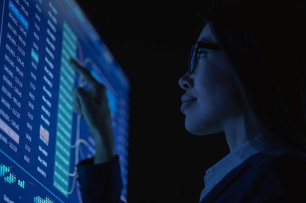 비즈니스 여성은 어두운 사무실에서 센서 모니터와 함께 일합니다.