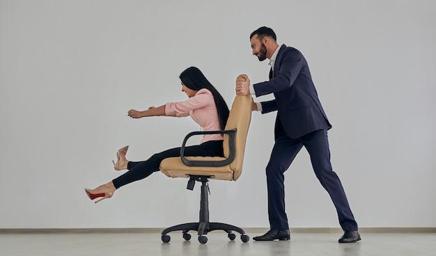 Деловой мужчина и женщина, играя со стулом