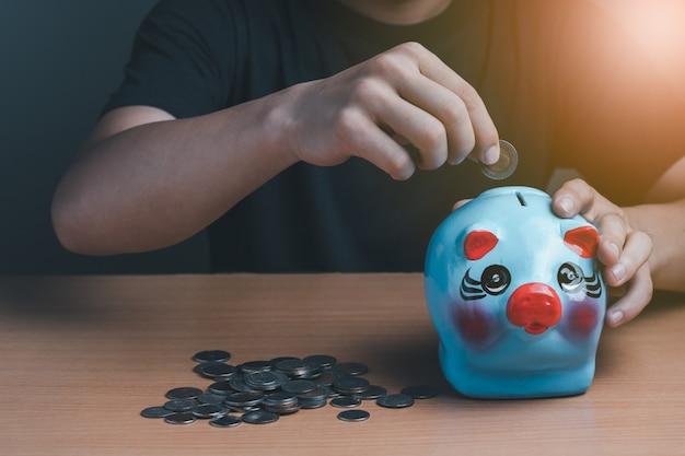 파란색 돼지 저금통에 동전을 넣고 나무 배경에 동전을 넣고 개념을 저장하고 투자하는 사업가