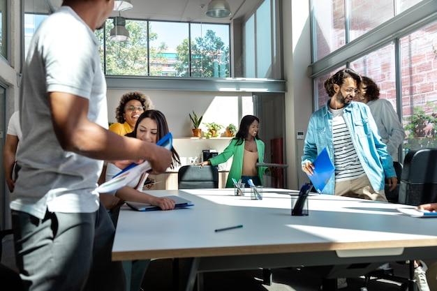 비즈니스 회의가 끝났습니다. 다인종 동료들이 일하기 위해 일어서서 비즈니스 회의