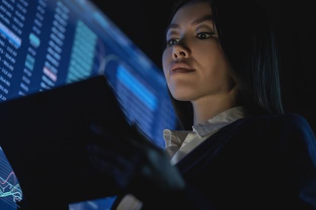 어두운 사무실에서 태블릿을 들고 있는 비즈니스 우먼