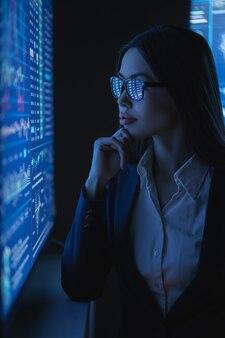 비즈니스 우먼은 차트가 있는 큰 블루 스크린을 봅니다.