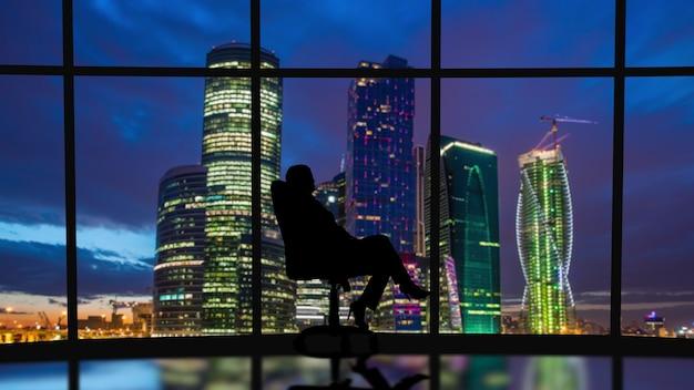 Деловая женщина сидит в офисе у окон с видом на ночной город