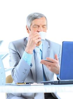 휴식 시간에 커피를 마시는 나이의 사업가. 흰색 배경에 고립.