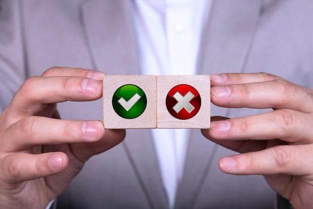 사업가는 예 및 아니오 아이콘이있는 두 개의 큐브 중에서 선택합니다.