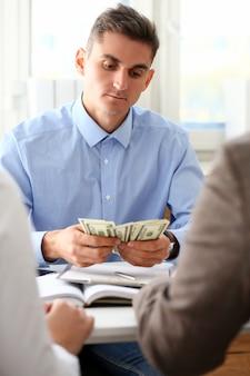 ビジネスマンはオフィスで現金ドルを検討します