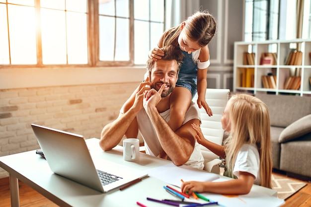 Папа-бизнесмен пытается работать за ноутбуком, когда его дочки играют, дурачатся и мешают ему. внештатный, работа на дому.