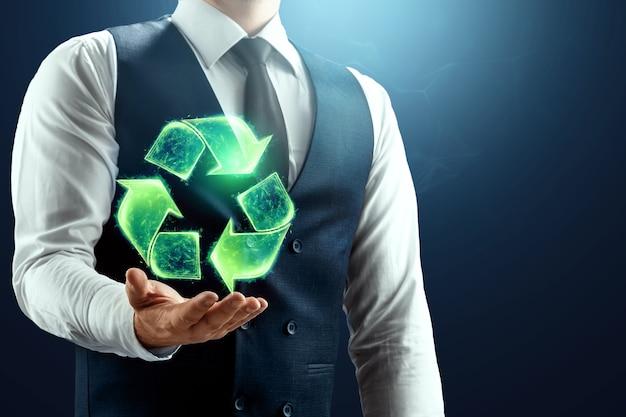 사업가는 손바닥에 재활용 아이콘의 홀로그램을 가지고 있습니다.