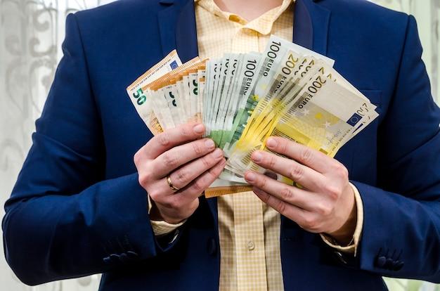 Бизнесмен держит в руках евро.