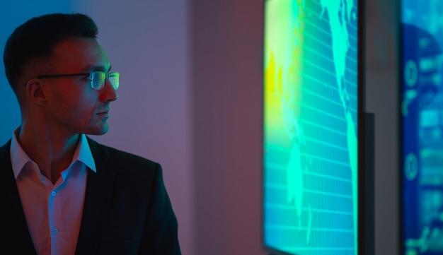 Бизнесмен в очках, стоящий возле экранов с графиками