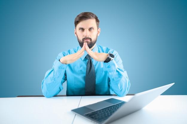 파란색 셔츠와 넥타이를 입은 사업가가 그 앞에서 손가락을 접었습니다.