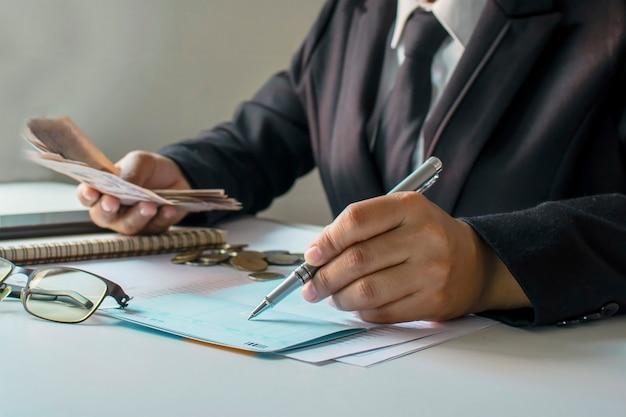 ビジネスマンは、財務および作業管理に関する会計および事業収入のアイデアを検討しています。ソフトフォーカス。